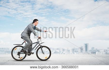 Businessman With Paper Documents In Hand On Bike. Deadline For Paperwork. Corporate Employee In Grey