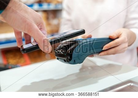 A Womans Hands Are Held By A Payment Terminal And A Man Pays For A Purchase Using A Smartphone. Side