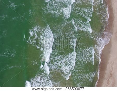 Top View Of Cold Stormy And Harsh Baltic Sea. Empty Off-season Beach Scene Photographed With A Drone