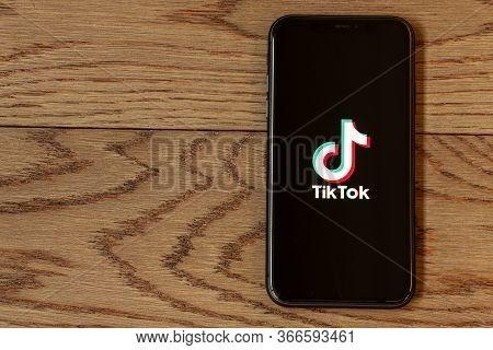 TikTok application icon on Apple iPhone 11 screen close-up. Hand holding smartphone Tik Tok icon on