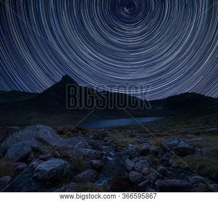 Digital Composite Image Of Star Trails Around Polaris With Stunning Vibrant Beautiful Landscape Imag
