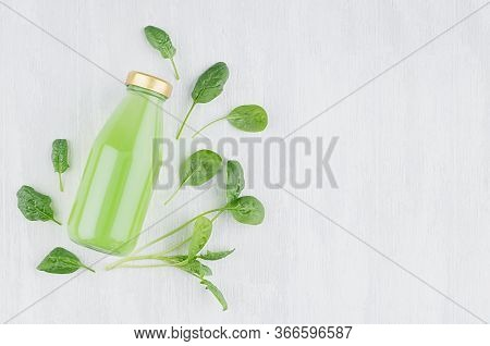 Organic Green Spinach Juice In Glass Bottle With Gold Cap, Fresh Leaves On White Wood Background, To
