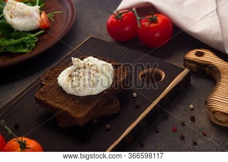 Healthy Breakfast Of Toast With Poached Egg, Tomatoes On A Dark Background And Chopping Board