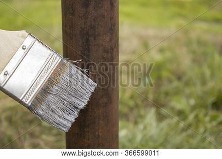 Paint Brush And Iron Post On The Background Of Grass. Brush With Gray Paint For Painting A Metal Col