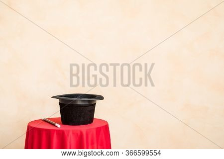 Magic Wand And Black Top Hat On Table Against Grunge Wall Background With Copy Space