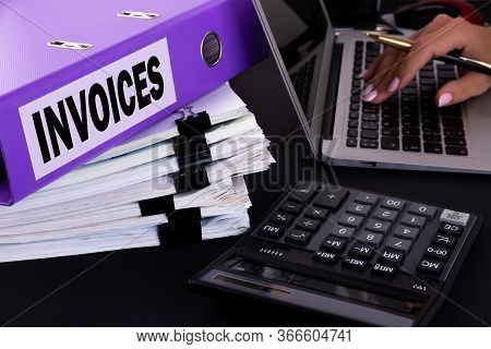 Text, Word Invoices Is Written On A Folder Lying On Documents On An Office Desk With A Laptop And A