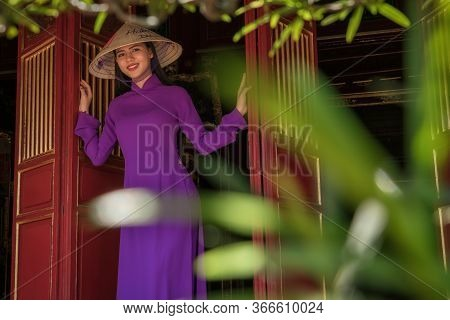 Hue, Vietnam - July 28, 2019 : Purple Woman Looking Out Of The Doors Of The Temple