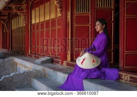 Hue, Vietnam - July 28, 2019 : Purple Woman Sitting On The Steps Of The Temple