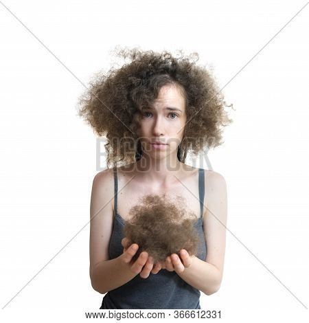 Girl Holds Her Lost Hair In Her Hands And Looks Disappointed. Fluffy Hair After Removing Dreadlocks.