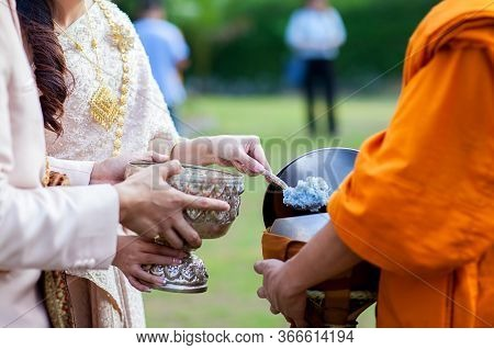 Offer Food To Monk. Groom Give Alms Food To A Buddhist Monk In Traditional Thai Wedding Ceremony. Ha
