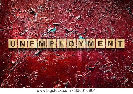 Unemployment. The Inscription On Wooden Blocks Against The Background Of A Red Cracked Wall. Unemplo