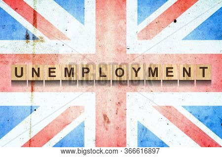 Unemployment. The Inscription On Wooden Blocks On The Background Of The Flag Of England. Unemploymen