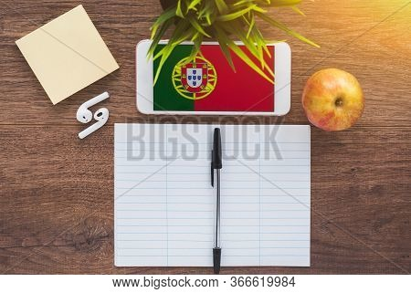 Portuguese Flag On Smartphone On A Wooden Table, Notebook And Pen, Study Concept