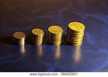 Stacks Of Ukrainian Coins On A Blue Background. 2, 10, 25, 50 Ukrainian Kopecks In Stacks.