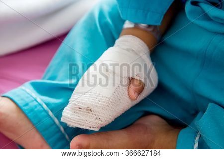 Children Illness . A Little Baby Attaching Intravenous Tube To Patient\'s Hand In Hospital Bed.kid H