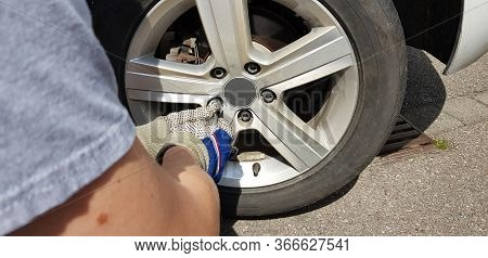 Young Man Changes And Repairs His Tires On The Car