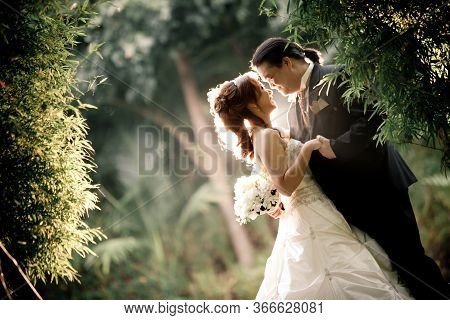 Wedding Couple Enjoying Romantic Moments Outsides On A Summer. Happy Bride And Groom On Their Weddin