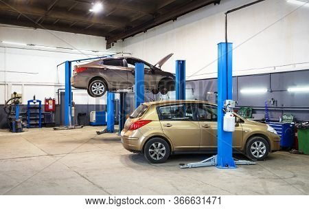 Car On Lift In Mechanic Shop Or Garage, Interior Of Auto Repair Workshop, Vehicles Inside Maintenanc