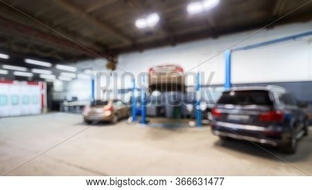 Auto Repair Workshop Interior In Bokeh, Blurred Defocused Background. Car On Lift In Mechanic Shop O