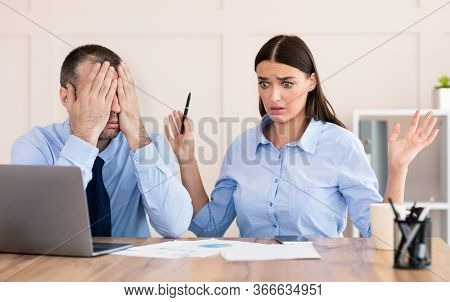 Professional Incompetence. Businessman Covering Eyes Unable To Train Silly Intern Girl Sitting In Mo