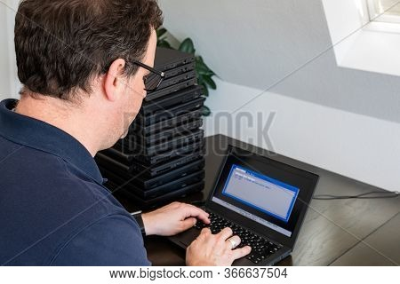 A Casually Dressed Caucasian Middle Aged Man Is Installing A Laptop Computer With A Stack Of Several