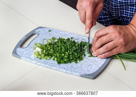 Closeup Hands Holding Knife Chopping, Cutting Green Onion. Sliced Fresh Green Onion. Cooking Vegetab