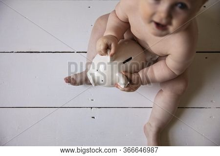 A Baby Holding Onto A Piggy Ban Money Box. Childcare Costs Concept
