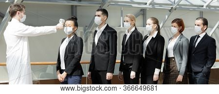 Doctor Wearing Protective Surgical Mask Using Infrared Forehead Thermometer (thermometer Gun) To Che