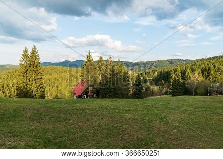 Mountaiin Scenery With Isolated Houses, Meadow And Hills Covered By Forest During Springtime Evening