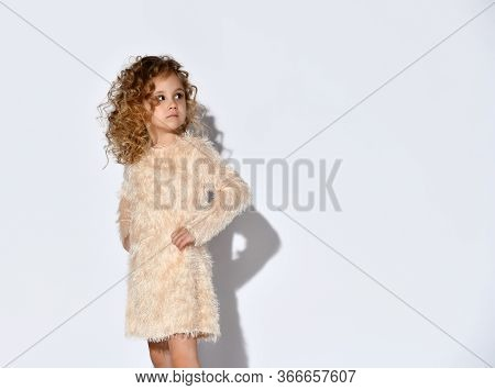 Little Curly Blonde Baby In A Fluffy Beige Dress. She Put Her Hands On Her Belt And Looks Away, Posi