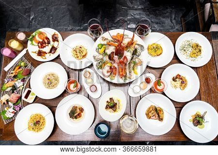 Table top view premium variety of international food in restaurant of lobster shrimp steak beef lamb pasta spaghetti risotto rice sushi sashimi and wine using for buffet food drink background.