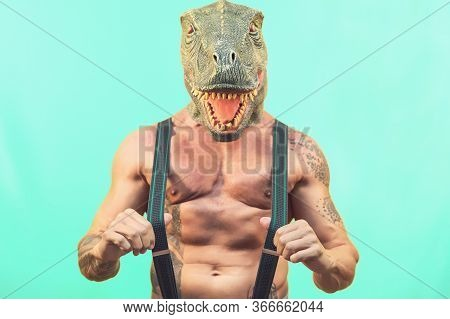 Fit Senior Man Wearing T-rex Dinosaur Mask - Crazy Hipster Guy Having Fun Celebrating Masquerade Car