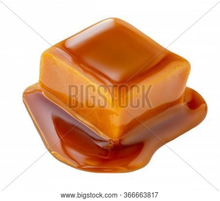 Caramel Sauce Flowing On Caramel Candies, Isolated On White Background. Golden Butterscotch Toffee C