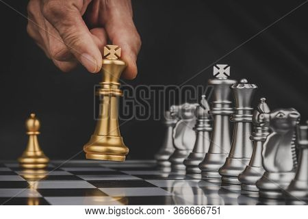 Businessman Hand Moving Gold King With Silver Chess Pieces On Chess Board Game Competition On Dark B