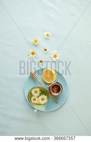 Chamomile Flowers And Chamomile Tea. Chamomile Tea In Glass Teacup With Flowers, Honey And Lemon, To