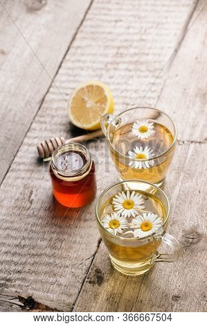 Chamomile Flowers And Chamomile Tea. Chamomile Tea In Cup With Flowers, Honey And Lemon, Close-up. S