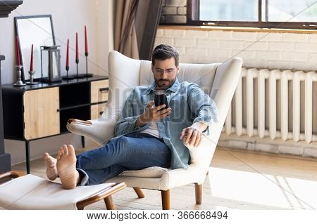 Millennial Man Relax In Chair Using Cellphone Device