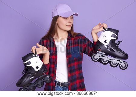 Indoor Shot Of Female Posing Against Lilac Studio Wall With Rolling Skates In Hands, Looking Concent
