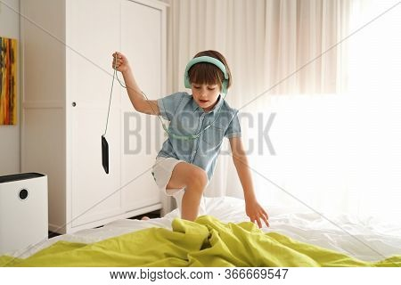 Cute Little Boy Wearing Huge Headphones And Listening To The Music In His Room. Child Having Fun Lis