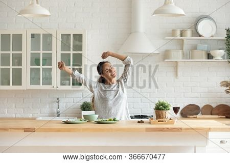 Happy Millennial Woman Have Fun Cooking Breakfast In Kitchen