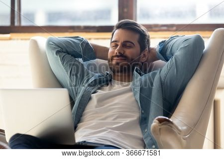 Millennial Man Relax In Cozy Chair Daydream In Living Room