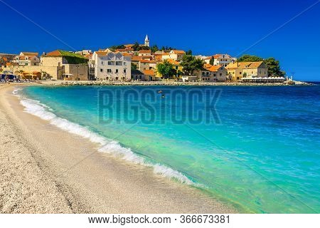 Picturesque Sandy Beach Resort With Waves And Old Mediterranean Buildings In Background, Primosten,