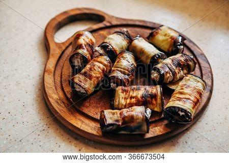 Stuffed Eggplant Rolls Lie On A Cutting Board.