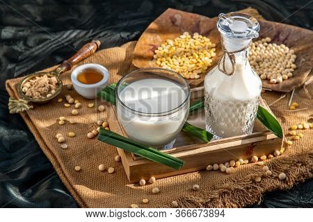 Soy Products : A Glass Of Homemade Soy Milk And Grains (soybeans) In Wooden Tray Served With Brown S