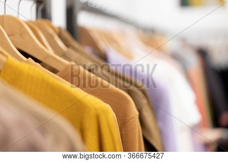 Multi Colored Clothing Shirts Hang On Hangers In A Shop Background. A Variety Of Clothes Hanging In