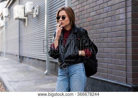 Beautiful Young Stylishly Dressed Caucasian Girl Smokes Cigarette On Street Smoking Bad Habit Nicoti