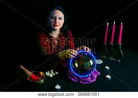 A Young Clairvoyant And Fortuneteller Divines Over A Mirror Ball In A Magic Salon On A Black Backgro