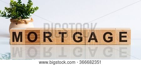 Mortgage Word Written On Wood Block. Mortgage Text On Wooden Table For Your Desing, Concept. Flower