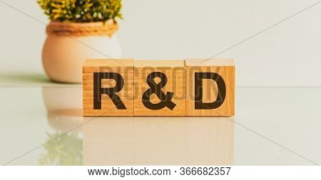 Three Wooden Cubes With Letters R And D On White Board. Flower In The Background On The Left.