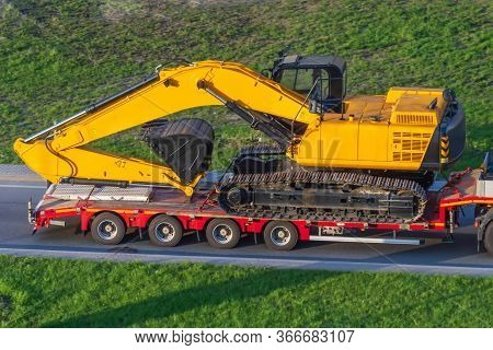 Heavy Yellow Excavator On Transportation Truck With Long Trailer Red Platform On The Highway In The